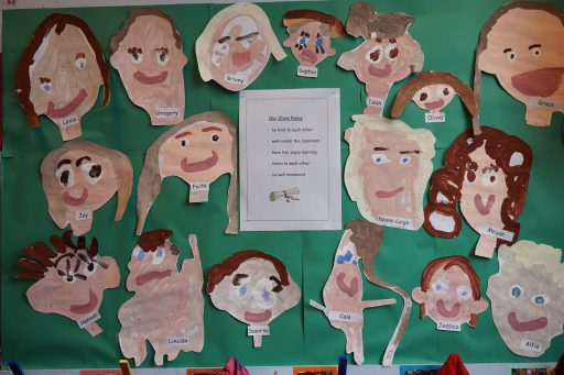 Reception childrens self portraits and class rules on Reception welcome board